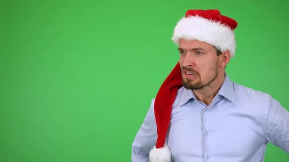 Thumbnail for A Young Handsome Man in a Christmas Hat Acts Angry - Green Screen Studio