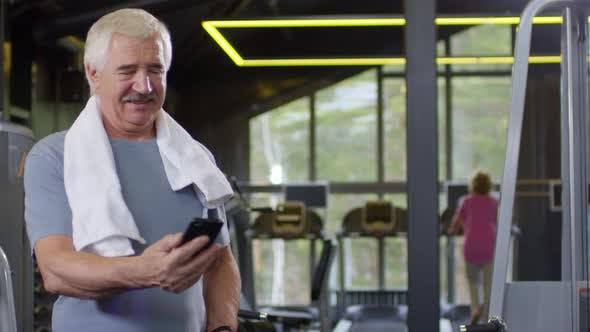 Thumbnail for Old Man Using Phone in Gym