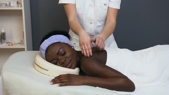 Thumbnail for Afrikanische junge Frau während der Massage im Spa Salon