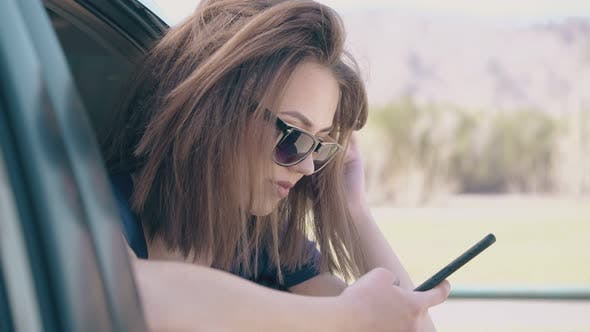 Thumbnail for young woman uses mobile phone leaning out of car window