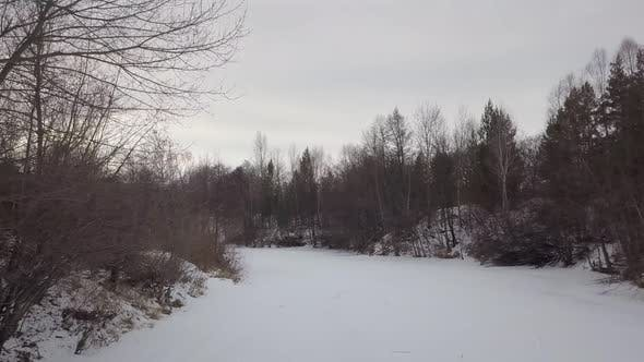 Thumbnail for Drone Is Flying Low Over Frozen Snowy River in Forest in Winter Day