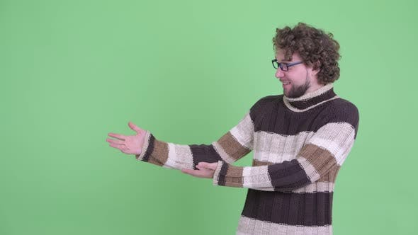 Thumbnail for Happy Young Bearded Man Showing Something and Looking Surprised