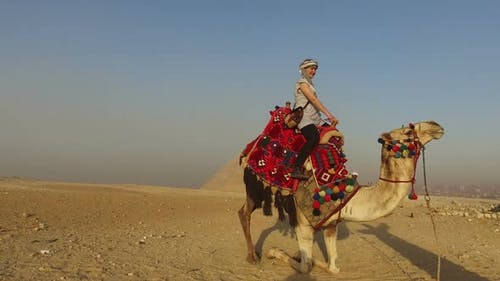 Woman on top of camel back while camel is getting ready to sit down