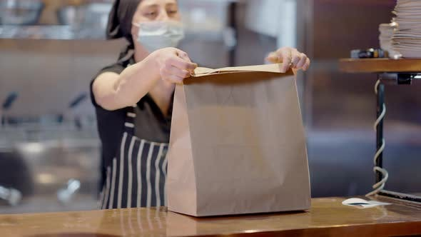 Blurred Caucasian Young Woman in Covid Face Mask Packing Takeaway Food in Cafe or Restaurant