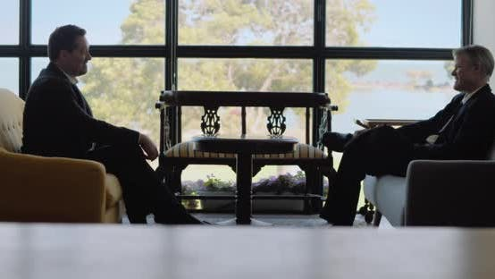 Two businessmen having a friendly meeting in a hotel lobby. Real time, long shot.