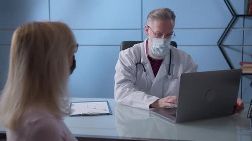 Professional Serious Focused Middle Aged Hoary Physician in Medical Mask and Coat Sitting at Table