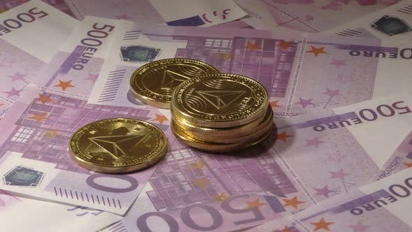 Gold Tron Coin TRX Coins Rotating on Bills of 500 Euro Banknotes. Worldwide Virtual Internet