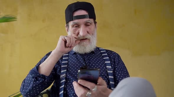 Thumbnail for Bearded Stylish Man in Youthful Cap which Using His Smartphone