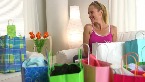Thumbnail for Middle aged woman looking through shopping bags