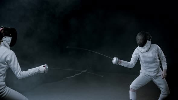 Thumbnail for Fencing Training - Two Women Having a Duel in the Dark Studio