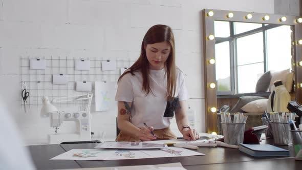 Female Designer Drawing Fashion Sketch in Sewing Studio