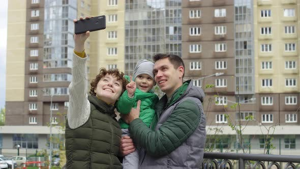 Thumbnail for Urban Family Taking Selfies in Front of High-Rise Apartment Block