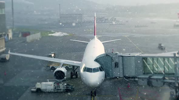 Cover Image for Commercial Airplane Standing at Airport Terminal in Winter Weather