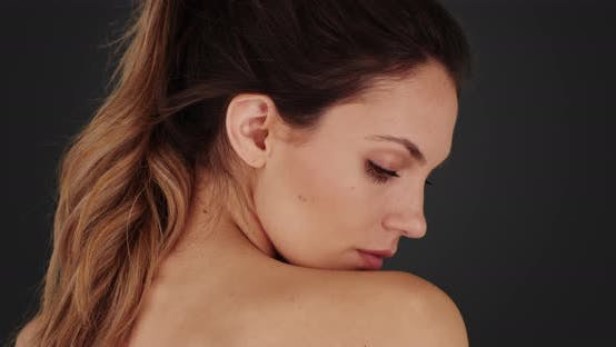 Thumbnail for Gorgeous woman turning head and looking at camera on solid gray background