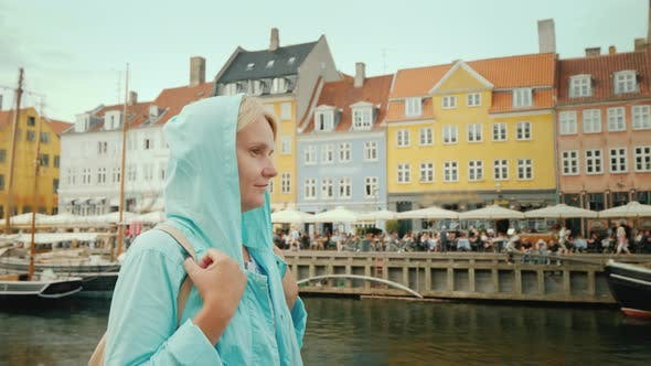 Thumbnail for Side View of A Woman Strolls Along the Nyhavn Canal, Against the Background of Famous Colorful