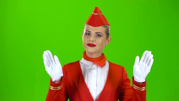 Thumbnail for Stewardess Gestures Where the Emergency Exit Is. Green Screen