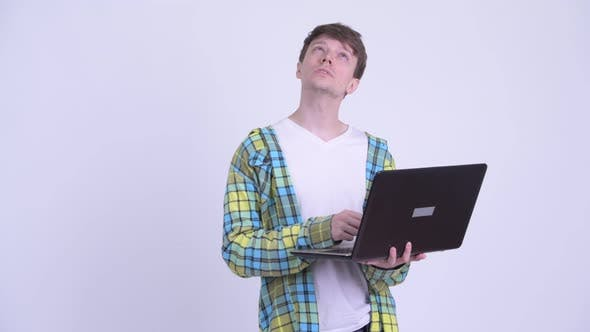 Cover Image for Happy Young Handsome Man Thinking While Using Laptop