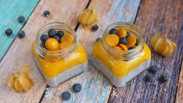 Thumbnail for Coconut Mango Chia Seed Pudding With Physalis And Blueberry.