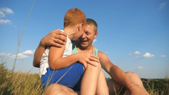 Thumbnail for Smiling Red-haired Boy Sitting at Green Grass on the Lawn with His Father and Having Fun Together