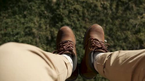 Flying Over the Beautiful Forest Trees. Aerial Camera Shot and Human Legs with Blue Sneakers in
