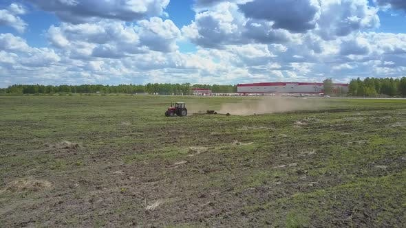Thumbnail for Tractor Operates on Field Birds Peck Grain on Sunny Day