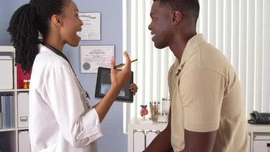 Thumbnail for African American doctor talking to patient with tablet computer