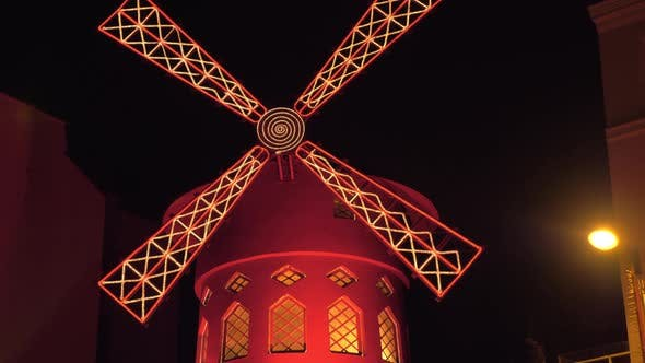 Moulin Rouge night view in Paris Spinning red mill