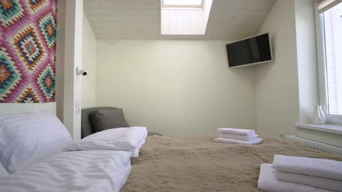 Interior of a spacious hotel bedroom on attic floor with fresh linen on a big double bed. Cozy