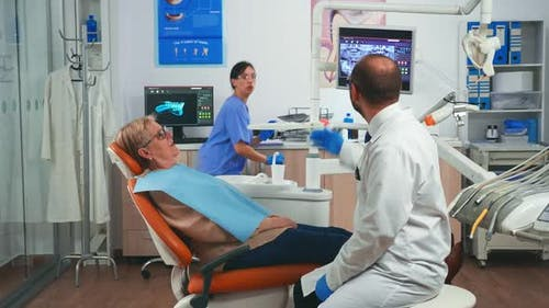 Doctor Discussing a Plan for Denture Recovery Looking at x Ray
