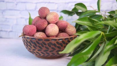 Lychee in Bowl with Leafs on Wooden Background