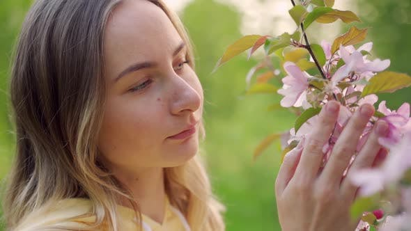 Thumbnail for The Smell of Flowers in the Spring Garden. Attractive Girl Touches Flowers