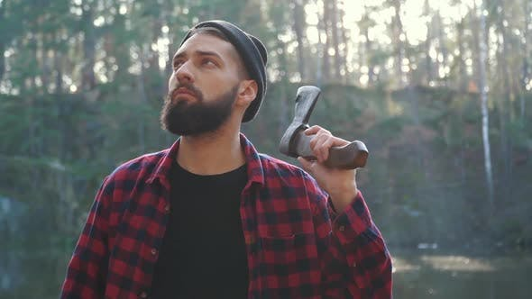 Thumbnail for Young Bearded Man with an Axe Walk in Forest. Unshaven Forester with an Ax Outdoors.