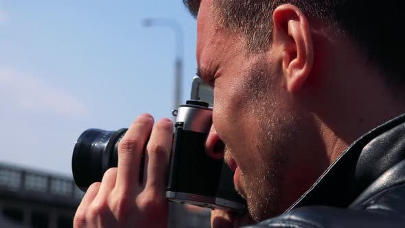 A Young Handsome Man Takes Photos of an Urban Area with a Camera - Face Closeup From the Side