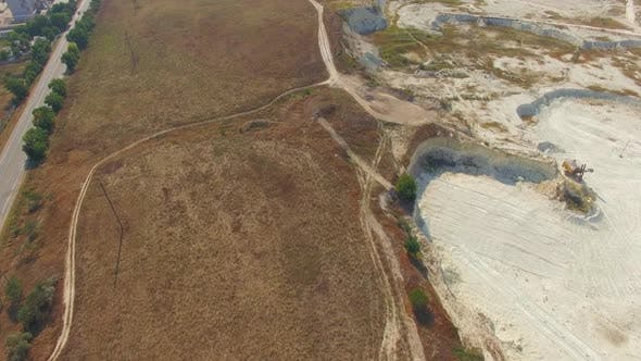 Quadrocopter Flies Over Field and Quarry