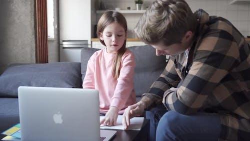 Kind-Tochterin, die virtuelle Online-Klasse bei Videoanrufen mit Papa zu Hause lernt