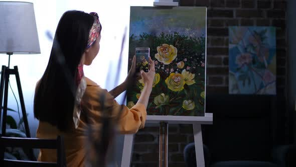 Female Painter Photographing Artwork with Peonies