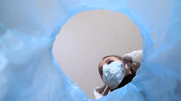 Thumbnail for Woman Doctor in Medical Gloves Takes Off Her Disposable Face Mask and Throws Into the Trash Can.