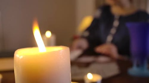 Close-up of Lighting Candle Standing on the Table As Blurred Caucasian Woman Taking Out Cards