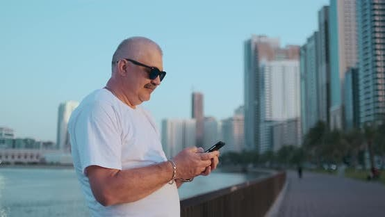 Thumbnail for Bearded Senior Man Standing Outdoors Using Smartphone. Retired Male Reading News, Chatting