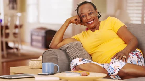 Thumbnail for An older black woman is very happy as she poses for a  portrait while sitting on her couch
