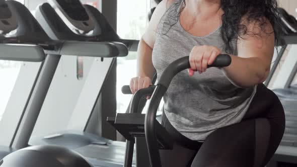 Thumbnail for Lovely Cheerful Plus Size Woman Smiling To the Camera Exercising on Air Bike