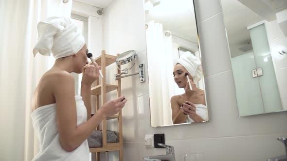Makeup. Woman Applying Powder On Face Skin At Bathroom