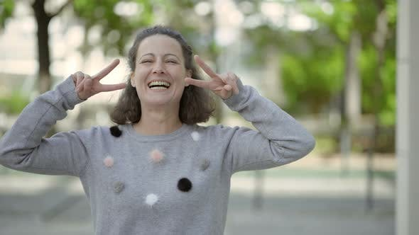 Thumbnail for Beautiful Smiling Middle Aged Woman Showing Peace Signs