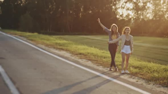 Thumbnail for Pretty Women Travelers Waiting for Car s at Roadside. Young Sexy Girls Dressed in Casual Summer