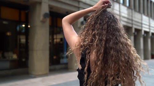 Verspielte junge Frau läuft in der Stadt, posiert auf der Straße für Kamera und flirtet
