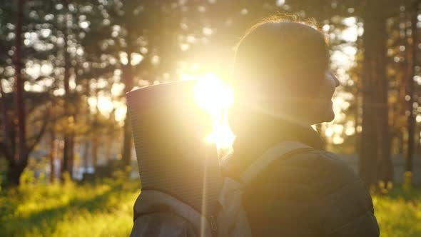 Happy Young Woman with Backpack in Sunset Light in a Forest. Sun Glare