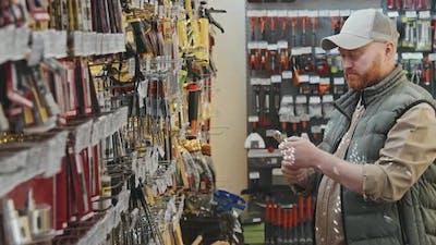Guy Choosing Tool at Hardware Store