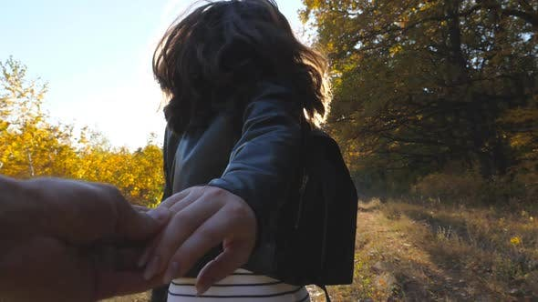 Thumbnail for Follow Me Shot of Happy Girl Leads Her Boyfriend Along Trail Near Autumn Forest. Young Woman Holds