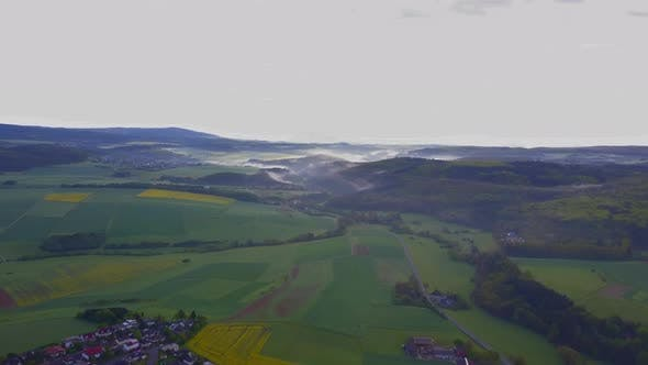 AERIAL: Flight Over German fields,town,Nature with Foggy Landscape in the Back, Sunshine, Fog
