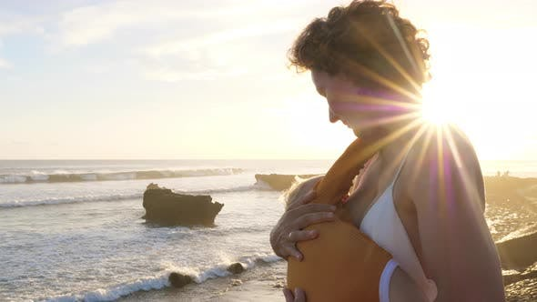 Young White Mother Breastfeeding Her Child Watching the Ocean on a Sunrise